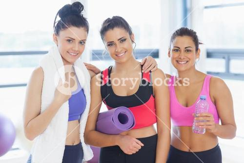 Three fit young women smiling in exercise room