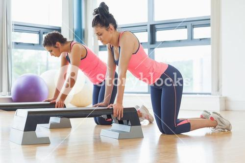 Fit women performing step aerobics exercise in gym