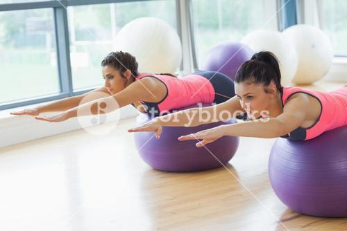 Two fit women stretching out hands on fitness balls in gym