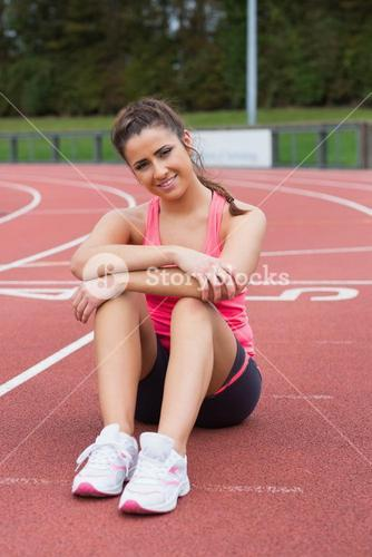 Sporty woman sitting on the running track