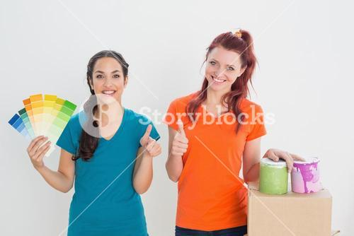Friends gesturing thumbs up with swatches, box and paint cans