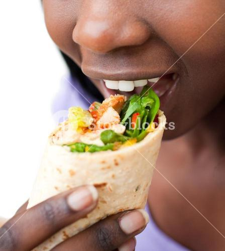 Close up of a woman eating a wrap