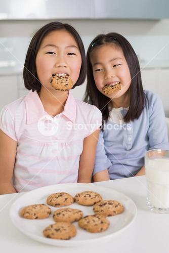 Two girls enjoying cookies and milk in kitchen