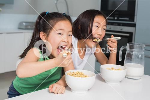 Two smiling young girls eating cereals in kitchen