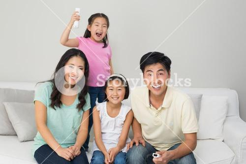 Happy family of four watching tv in living room