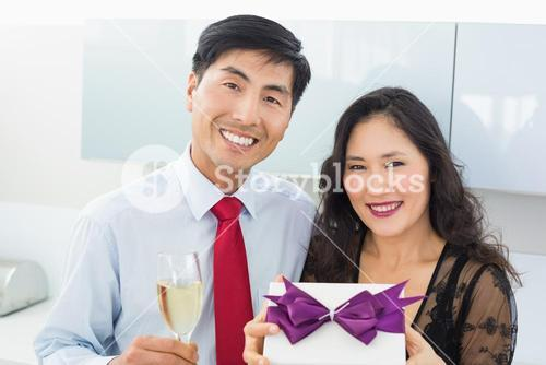 Portrait of a happy young couple with a gift box and champagne