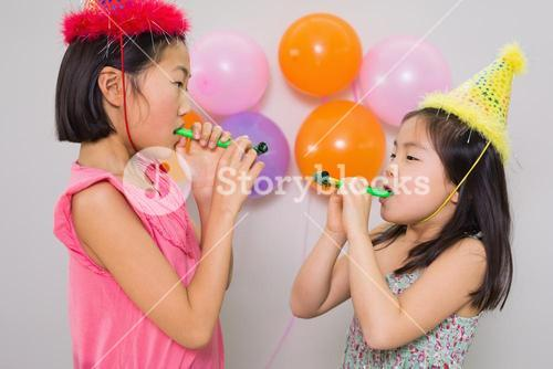 Girls blowing noisemakers at a birthday party
