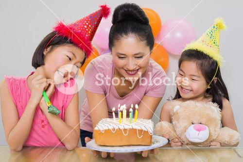 Girls looking at mother with cake at a birthday party