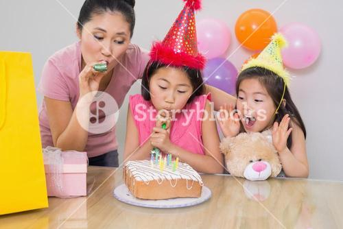 Girls and mother blowing noisemakers at a birthday party