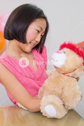 Cute girl with her soft toy at a birthday party