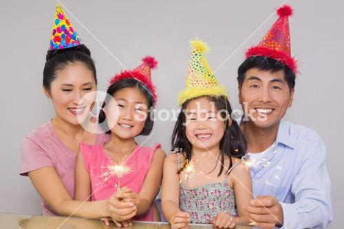 Family of four playing with firecrackers at a birthday party