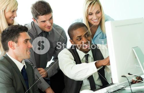 Manager explaining a job to his team from a computer