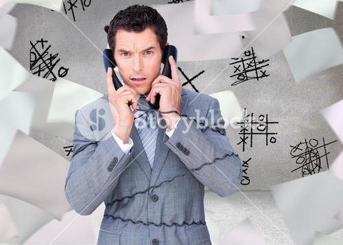 Composite image of angry businessman tangle up in phone wires