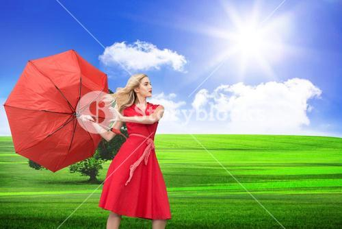 Composite image of beautiful woman posing with a broken umbrella