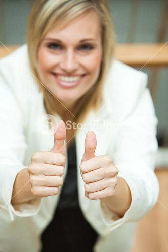 Businesswoman smiling at the camera with her thumbs up