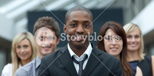 Businessman smiling at the camera with his team
