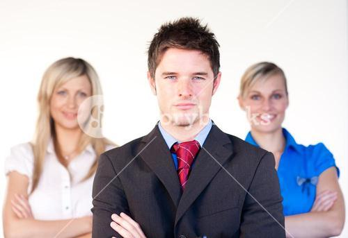 Confident businessman with businesswomen in the background