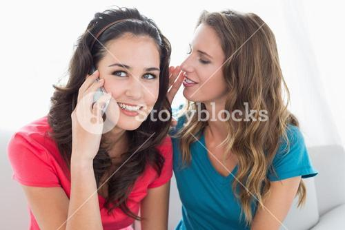 Female friends using mobile phone at home