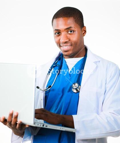 Handsome doctor working on a laptop and smiling at the camera