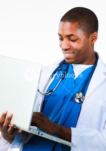 Friendly doctor working on a laptop