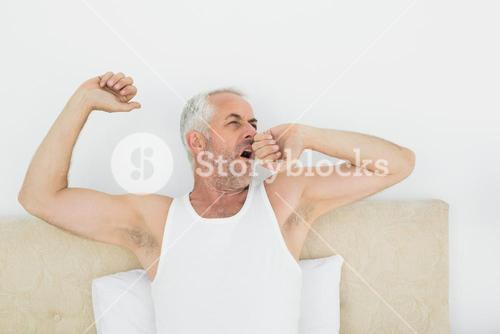 Mature man stretching arms in bed