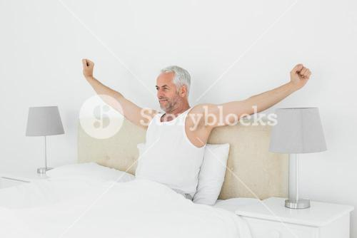 Mature man stretching his arms in bed