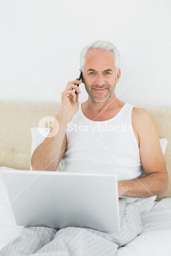 Smiling mature man using cellphone and laptop in bed