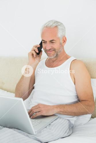 Mature man using cellphone and laptop in bed