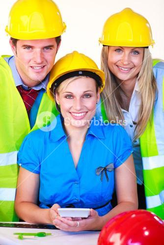 Team of three with hard hats at work smiling at the camera