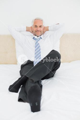 Portrait of a relaxed mature businessman sitting in bed
