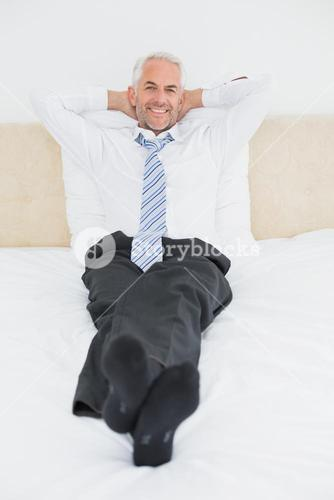 Relaxed mature businessman sitting in bed