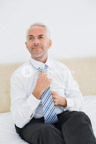 Thoughtful businessman adjusting neck tie in bed