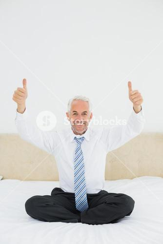 Happy mature businessman gesturing thumbs up on bed