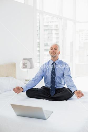 Businessman sitting in lotus pose with laptop on bed