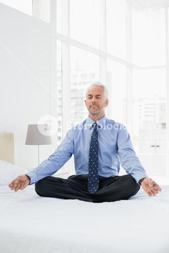 Relaxed mature businessman sitting in lotus posture on bed