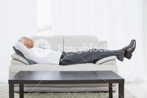 Tired mature businessman sleeping on sofa in living room