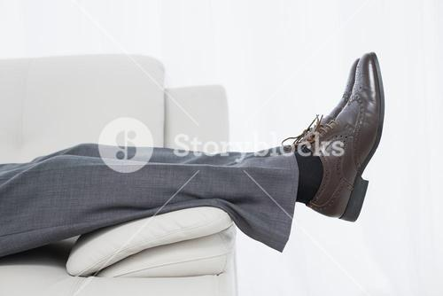Low section side view of a businessman resting on sofa