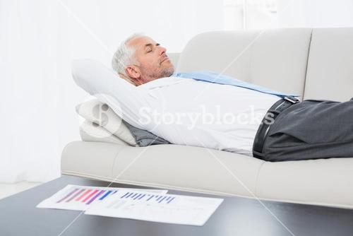 Businessman sleeping on sofa with graphs on table in living room