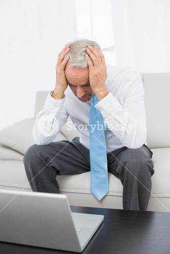 Worried mature businessman with laptop at home