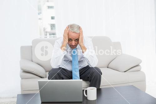 Portrait of a worried mature businessman with laptop at home