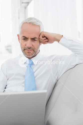 Mature businessman using laptop on sofa in living room