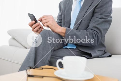 Mid section of a well dressed man text messaging at home
