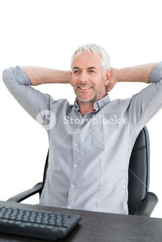 Businessman sitting with hands behind head at desk