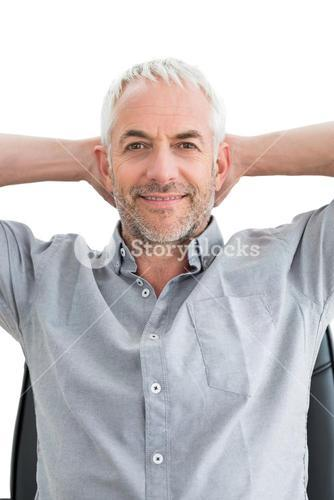 Relaxed mature businessman with hands behind head