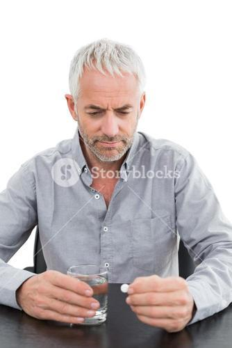 Serious mature man holding glass of water and pill at the table