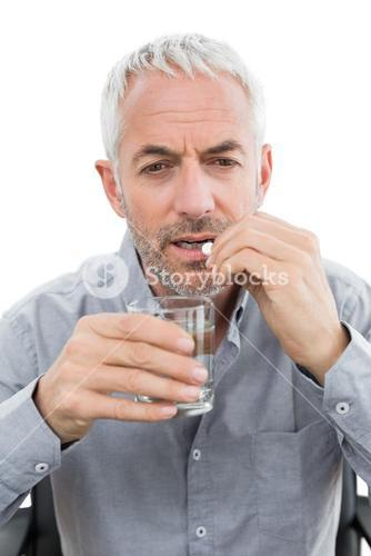 Closeup of a mature man with glass of water and pill