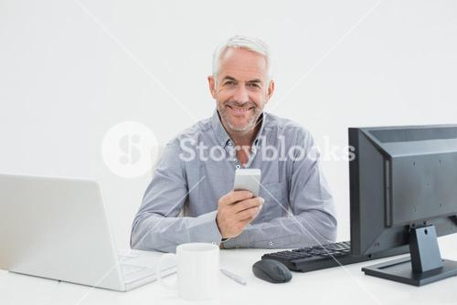 Businessman with cellphone, laptop and computer at desk