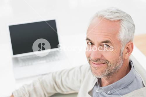 Closeup portrait of a grey haired man with laptop