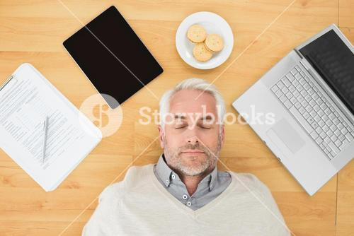 Mature man sleeping with electronics and biscuits on parquet floor
