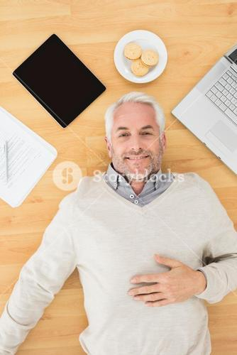Man lying with electronics and biscuits on parquet floor